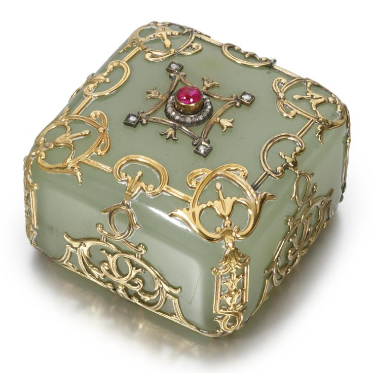 A FABERGÉ CARVED BOWENITE BELL PUSH WITH GOLD AND JEWELED MOUNTS, WORKMASTER MICHAEL PERCHIN, ST. PETERSBURG, CIRCA 1895-1899 of square shape with rounded corners, the bowenite set within a cage of scrolling gold floriated mounts, the top set with a cabochon ruby pushpiece surrounded by a collar of rose-cut diamonds and an applied gold floriated frame with diamonds set at the four corners