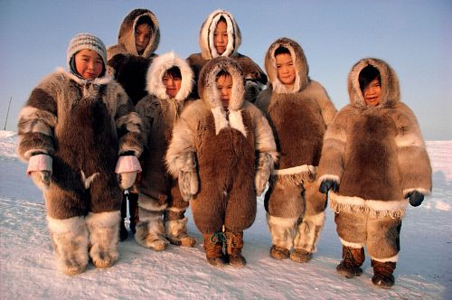Inuit children of the Taqqaugaq family dressed in caribou skin clothing. Baffin Is., Nunavut, Canada