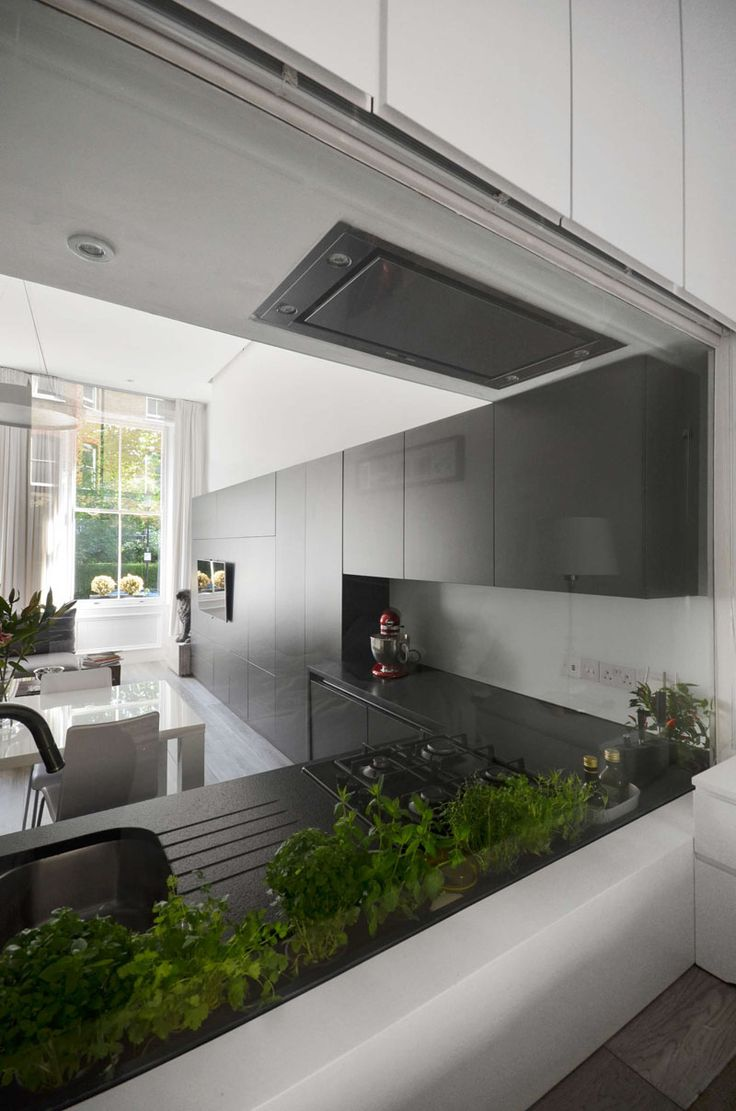 The black kitchen cabinets wrap around the wall and become the entertainment center in this apartment in London.