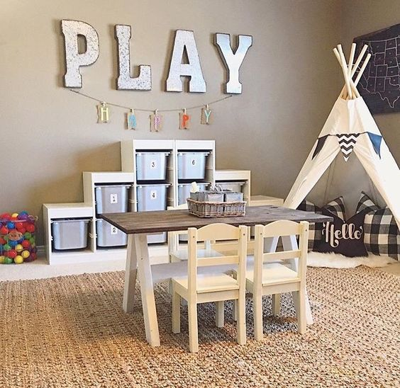 play area with a teepee, a table for drawing and a shelving unit with cubbies