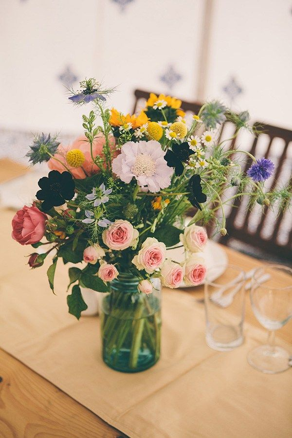 Leona and Ed Wedding Flowers - Sunflowers were mixed with daisies and wildflowers to create vibrant arrangements, which were displayed in jam jars.