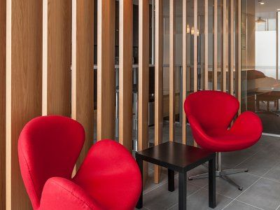 Timber panelling and curvy red chairs make a fashionable statement.