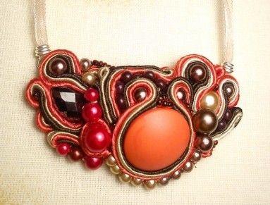 Vyšívaný soutache náhrdelník obsypaný perličkami v hnedej farbe s oranžovým gombíkom. Náhrdelník sa viaže vzadu na krku so stuškami na mašličku.