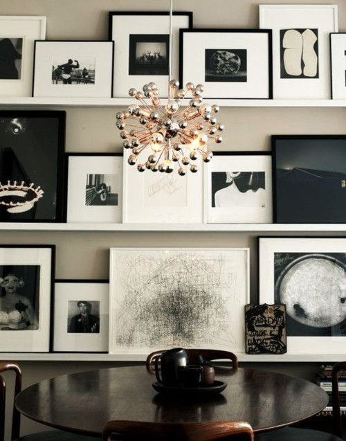 A wall of pictures and art on shelves. - I love this way of displaying pictures!