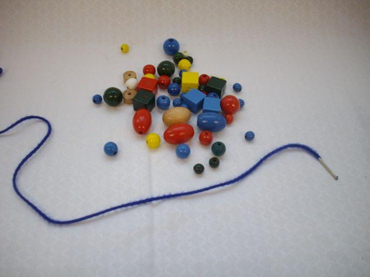 Titre: [Perles en bois].  Cote: JEU 2045 Description:  Comprend 50 perles en bois de forme et de couleur différente et 1 ficelle.  Résumé du catalogueur: Ces perles peuvent être utilisées pour apprendre les couleurs, apprendre à compter, apprendre les différentes formes, apprendre les formats, apprendre à enfiler.