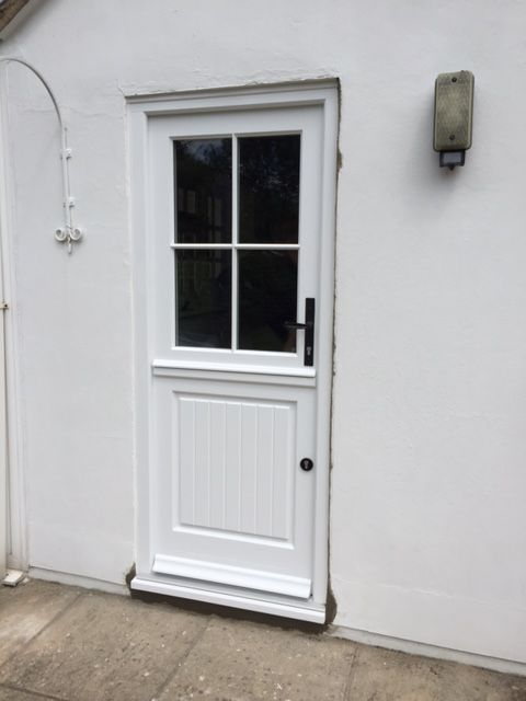 Stratfield style Timber stable door in White with Silver threshold. Featuring Black Kirkpatrick Handle and Black Escutcheon. Also with Astragal bars.