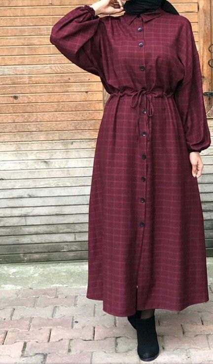 Hijabi wearing a buttoned gown and boots