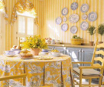 Plates Repeating Color: Decorating with plates gives you a good option for repeating colors within a room. The blue-and-yellow tablecloth fabric sets the color scheme, so yellow walls get a shot of interest from the blue plates arranged in an oval shape.
