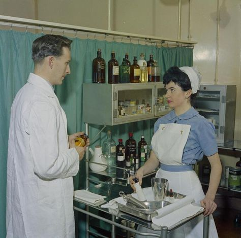 A scene in an RAF hospital. A nurse of the Princess Mary's Royal Air Force Nursing Service stands beside a trolley of equipment. The nurse is in discussion with a doctor.