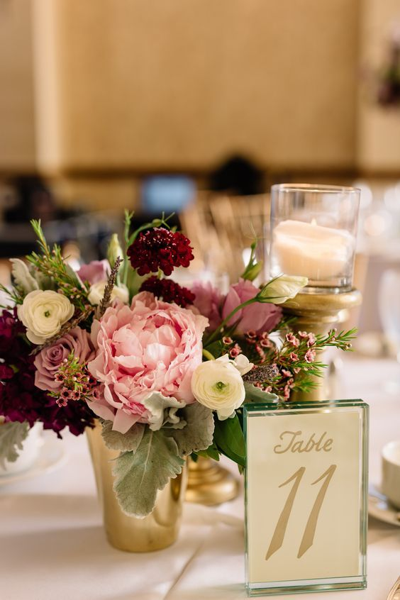 bridesmaids bouquets of pink peonies, lavender roses, burgundy scabiosa, lavender lisianthus,white ranunculus, and pink wax flower are repurposed at the reception tables in gold vases paired with a trio of pillar candles on mercury glass pedestals of varying heights.: