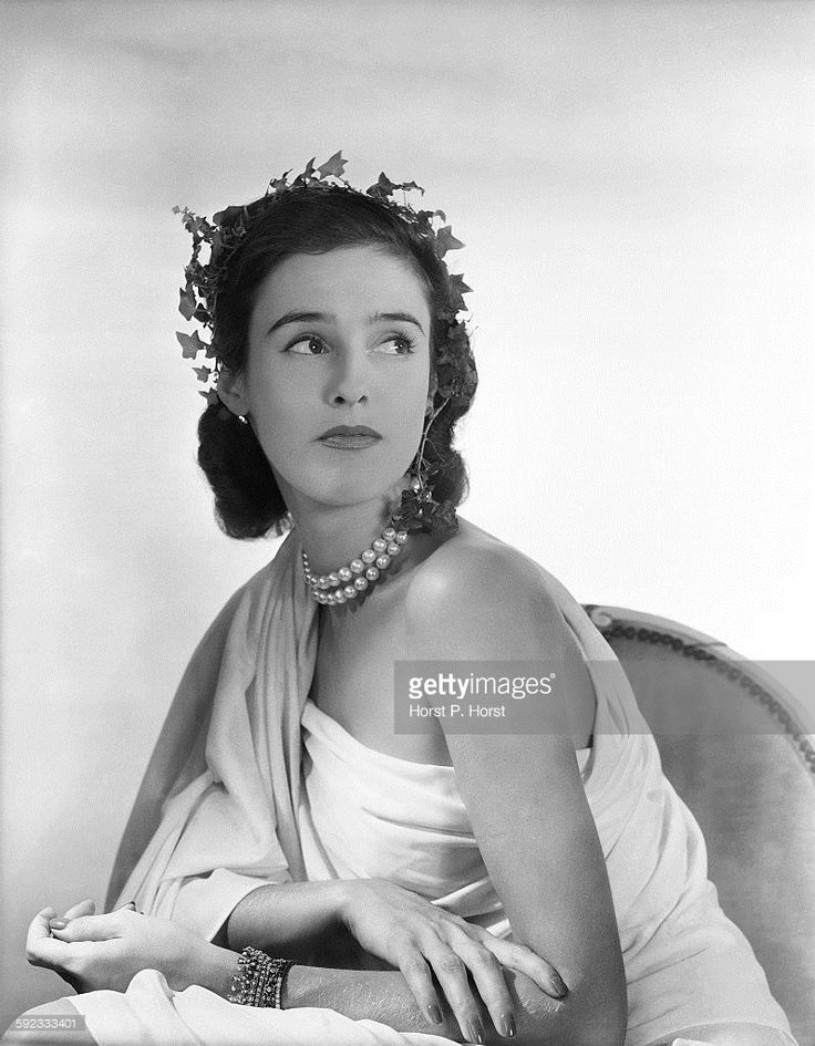 Portrait of Barbara Cushing Mortimer (aka Barbara Cushing, <a gi-track='captionPersonalityLinkClicked' href=/galleries/search?phrase=Babe+Paley&family=editorial&specificpeople=968974 ng-click='$event.stopPropagation()'>Babe Paley</a>, Barbara Cushing Mortimer Paley, Mrs Stanley Grafton Mortimer, Mrs William Paley). She is seated, wearing a one-shoulder gown, draped like a Roman toga, a double-strand pearl choker, and a wreath of ivy on her head.