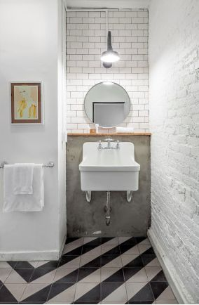 Utility sink, diagonal black and white floor tile pattern, barn house lighting, round bathroom mirror