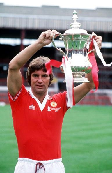 Martin Buchan holding the 1977 FA trophy aloft. At the time he was the first player to win the FA Cup and the Scottish cup