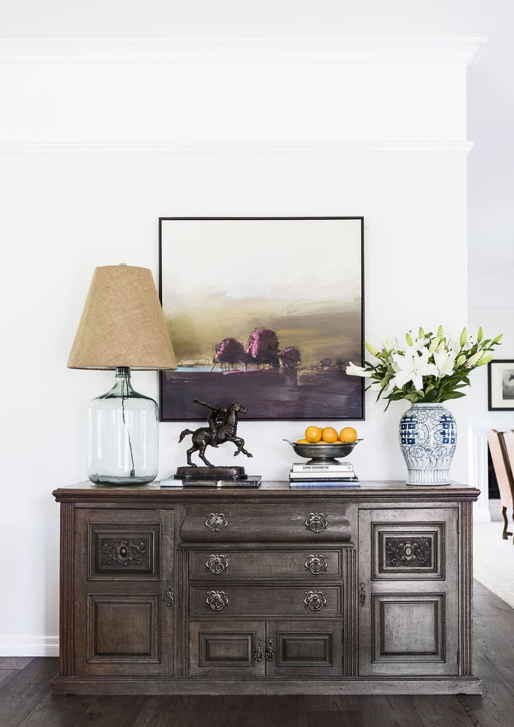 Antique chiffonier pared back with a hessian lamp shade and artwork at the 150-year-old renovated dairy farmhouse near Brisbane. Photography: Maree Homer | Stylist: Kate Nixon | Story: Australian House & Garden