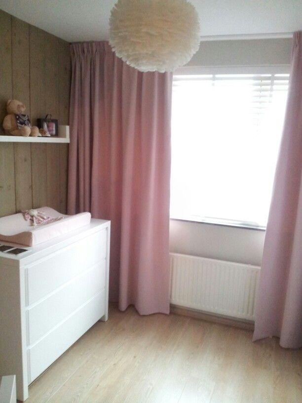 stoere lieve babykamer met ganzenveren lamp en houten panelen aan de wand lucht roze verdiusterende gordijnen combineren mooi met de hout