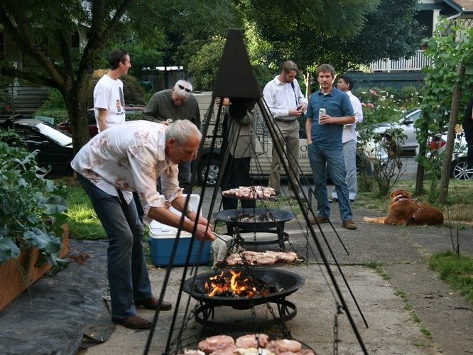Ewald Mosel grew up in Germany, where he cooked out on the schwenker every summer. The grill he uses hangs on a large tripod, suspended over the coals. With a little push from the schwenkmeister — that's Mosel — it swings back and forth, cooking the meat evenly.