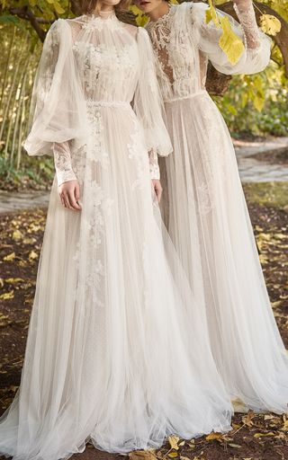 This **Costarellos Bridal** Neo-Romantic Tiered Long Dress features a mesh bodice with panels of Chantilly lace and full length sleeves with ruffled cuffs.