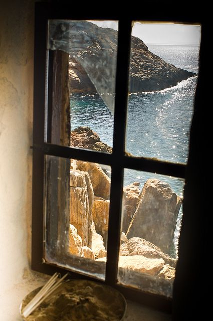 Ocean View, Syros, Greece  The window pane is framing the view, many would have just put their camera lens against the glass to take the photo of the ocean, eliminating the frame.  With the window frame it's a wow picture.