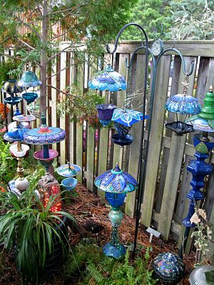 Whimsical bird feeders & ?...looks like recycled lamps & other found objects with very detailed painting....xo
