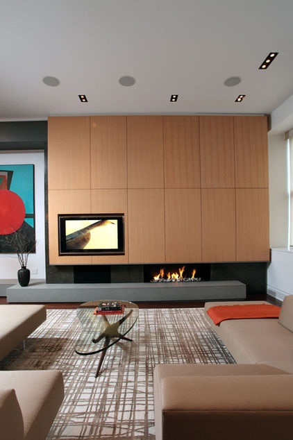 This living room artistically combines the television and fireplace on one wall. The television is offset by the hearth for balance, while the streamlined fireplace almost disappears under the recessed cavity when it's not on.
