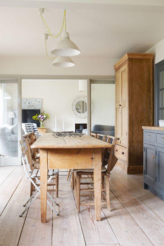 Сосновый деревянный стол в столовой. Столовая от гостиной отделена стеклянными дверьми.