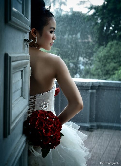 Love This Dramatic Image of Bride with Rain Falling In Background.