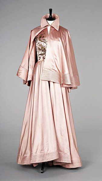 Description                     A rare and early Jacques Fath ball gown and matching cape, early 1940s, the gown labelled `Jacques Fath, Paris, of deep rose-pink satin