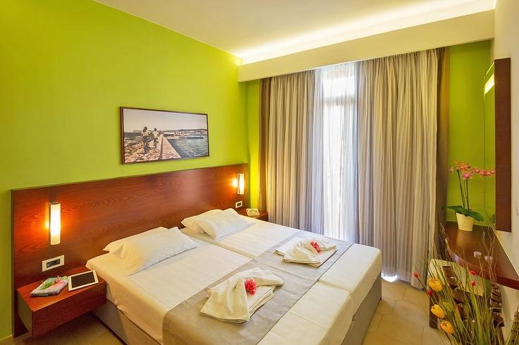 Oscar Suites & Village Studio room interior design. Double bed, night lamps, wall decor, wardrobe, private balcony