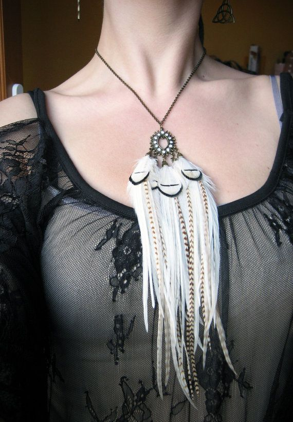 Necklace handmade on bronze mounting, closed by a carabiner.  This unique creation is made of 5 pendants of white feathers, redhead light and dark. The central connector in the form of mandorla is decorated with Rhinestone...
