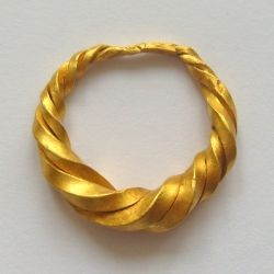 An ornate gold finger ring dating to the late Anglo-Saxon period. The ring is made up of three twisted gold rods which are rectangular in section, the ends of which are tapered and hammered together. The ring is of a type that is associated with the Vikings, & could be Scandinavian in origin. ID: 42246