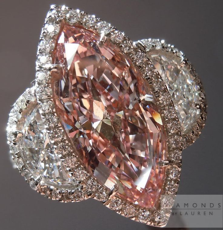 Fancy pink, marquise-shaped diamond ring with two half-moon white diamond accents and pave diamond work.