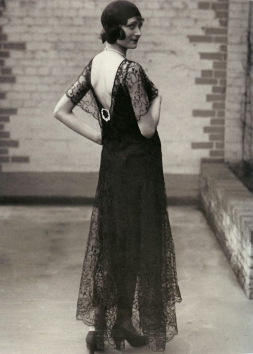 Девушка в длинном платье в стиле ретро 20-30 годов и туфлях на каблуках