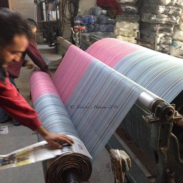And let's back up yet another step;  before a weaver can thread and set up their loom, they first have to make the roll of threads.  Here you see threads that have carefully been organized by the weaver to ensure the correct design is achieved.  They are then 'turned' onto an iron bar with pieces of newspaper rolled in for absorption of humidity.  The roll of threads will be set in place at the back of one of our larger towel looms.
