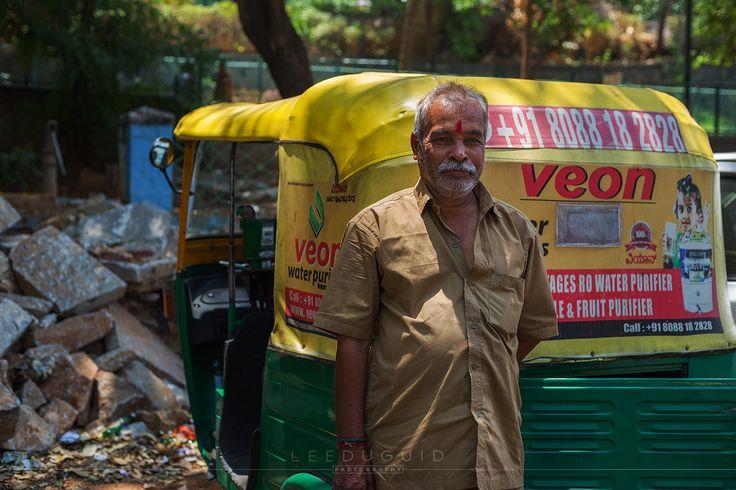 Auto / Tuk Tuk driver stands outside Sri Big Bull temple waiting for his next customer.