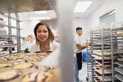 Pastry chef placing muffin tray on rack