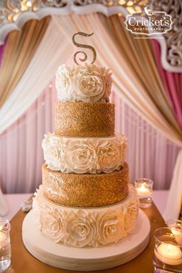 Cricket's Photography beautifully captured this glam ivory and gold buttercream wedding cake with lots of sparkle and ruffled rosettes for Candi & Mike's wedding at Champions Gate.
