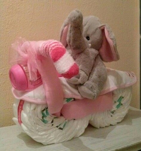 Moter gemaakt van luiers, luierdoeken, fles, slabbetjes en sokjes. Met een knuffel. De olifant zakt een beetje in omdat het een beany knuffel is. Die kan je warm maken in de magnetron en koelen in de vriezer.