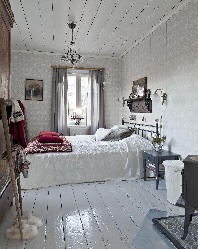 Pelkästään harmaan sävyillä sisustettu makuuhuone on yhtä aikaa kodikas ja harmoninen. Vanhan talon tyyliin kuuluu rautasänky, kamiina, vanha seinähylly ja puulattia.