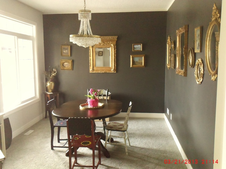 black dining room walls.  gold framed mirrors and gold framed pictures.  recycled brass chandelier.   hand painted chairs and pine table stained to look like mahogany