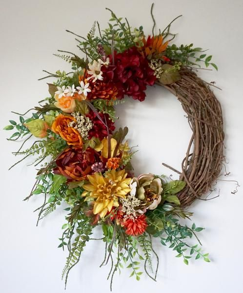 High quality fall wreath made with silk flowers. All flowers and greenery attached on a 18 inch grapevine wreath with floral wire and adhesive.                                                                                                                                                     More