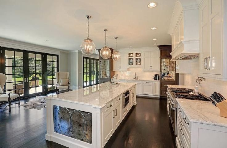 White and gray kitchen features three clear glass globe pendants illuminating a white center island fitted with antiqued mirrored side panels.