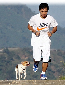 "Phillipino boxer Manny Pacquiao with his loyal workout partner, ""Pacman."""