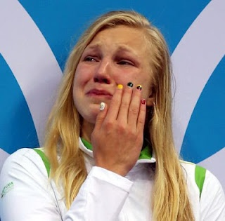 xunews: Ruta Meilutyte of Lithuania reacts as she receives her gold medal during the medal ceremony for the Women's 100m Breaststroke
