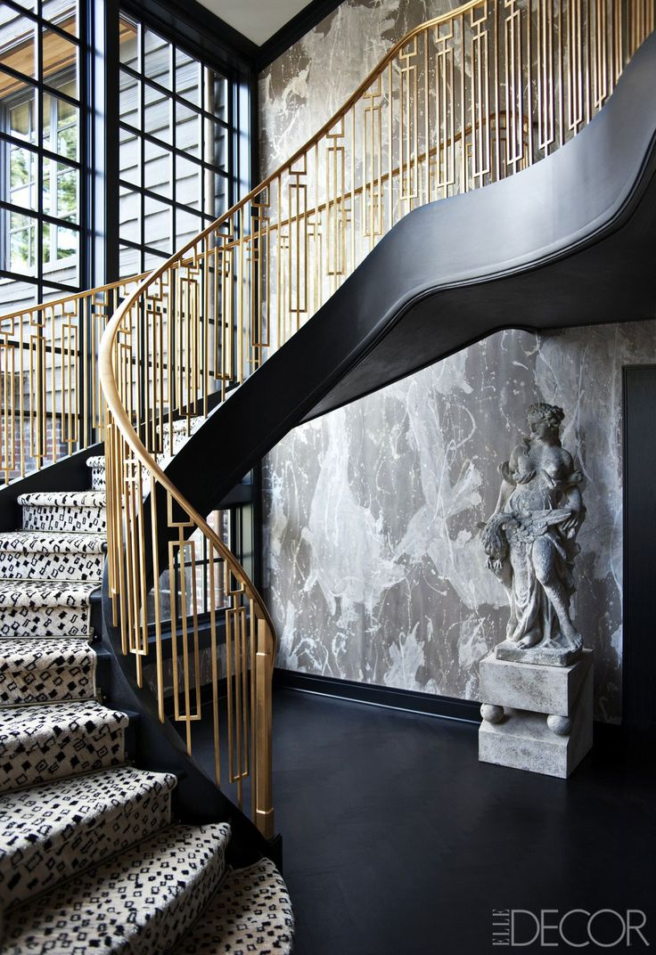 Dramatic staircase with brass railing steal the attention in this entryway.