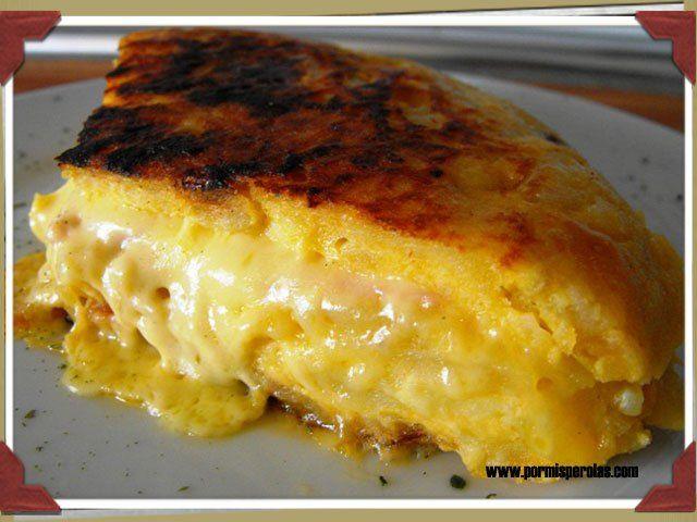 Tortilla de patata rellena con york i queso. Dividir la mezcla en dos partes. Hacer una tortilla i antes de girarla poner el york i el queso, seguido de la mitat de mezcla de la otra tortilla.