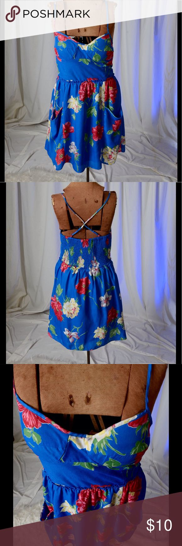 American Eagle blue dress with flowers American Eagle dress with flowers.  Dress has a large elastic panel in the back and criss-cross straps.  Dress has side pockets and is fully lined.  Cute! American Eagle Outfitters Dresses