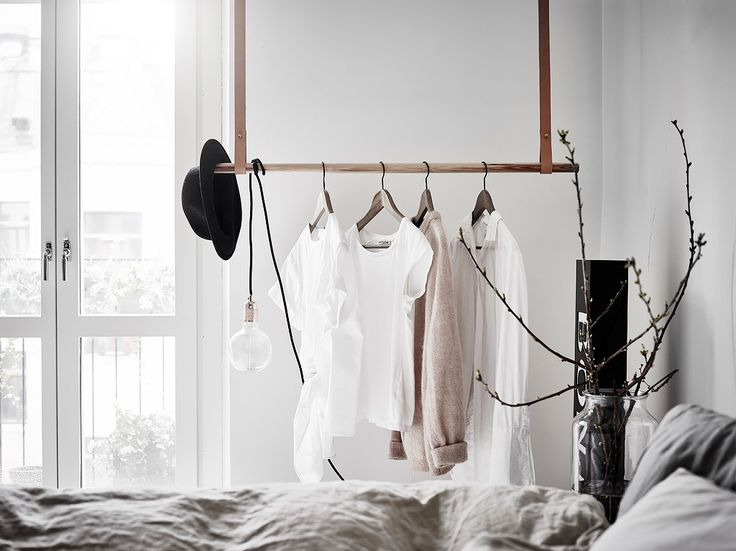 Cosy bedroom with hangers and leather straps. Scandinavian style.