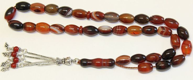 Presented here, a very elegant Tesbih - Masbaha - : OVAL YEMENI AGATE - AKEEK- in a very fine 33 bead strand.  It is an extremely pleasant item to use yourself or offer as a gift. It also has a very attractive and at a very reasonable price for such workmanship and type of material.  Description : Material : Oval Yemeni agate - akeek - of exceptional good quality . Tassel : Hand made Sterling Silver with red agate beads. Specially made for this strand Bead size 12 mm x 8 mm dia. Weight 47…