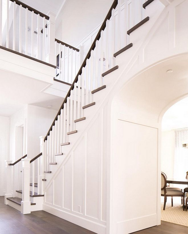 Foyer with dark hardwood floor and white paneling millwork and archway. Foyer…