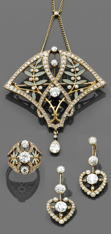 An Art Nouveau gold, enamel and diamond parure, by Masriera. Consists of a pendant with olive branch motifs, decorated with enamel, within a gold frame set with brilliant- and rose-cut diamonds, suspending a pear-shaped diamond, accompanied by a similarly designed ring, centring a brilliant-cut diamond, and a pair of heart shaped ear pendants, each set with brilliant-cut diamonds, mounted in gold. #ArtNouveau #Masriera